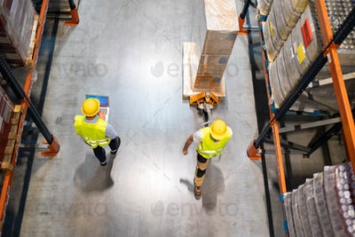 Warehouse worker with pallet truck and manager with laptop between shelves, above view
