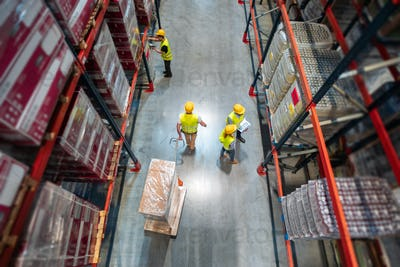 Working in warehouse group of workers with laptop, pallet truck and scanner