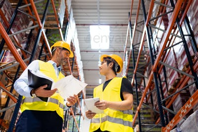 Warehouse workers checking inventory with plans in hand