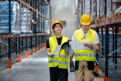 Warehouse workers checking delivery plans walking between the shelves
