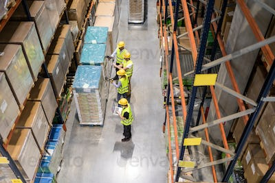 Group of warehouse workers scanning packages on pallets, view from above