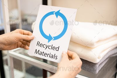 Hands of female shop assistant holding card saying about recycled materials
