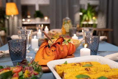 Part of served festive table with wineglasses, burning candles, homemade food