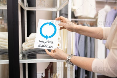 Shop assistant holding card saying about recycled materials by stack of sweaters