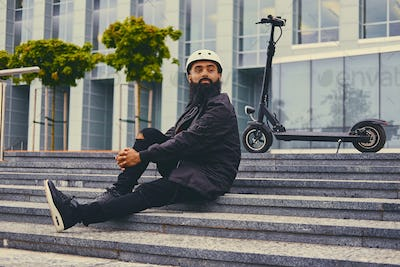 Bearded male on a step over electric scooter background.
