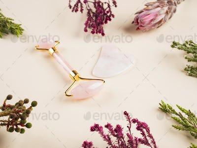 Quartz guasha face roller on floral background