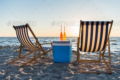 refreshing beverages on cooler and chaise lounges on sandy beach at sunset