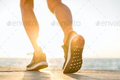 cropped shot of sportsman in modern sneakers running by seashore on senrise