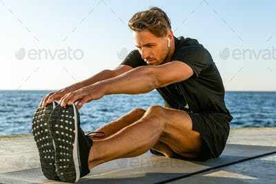 athletic adult man with wireless earphones stretching on seashore