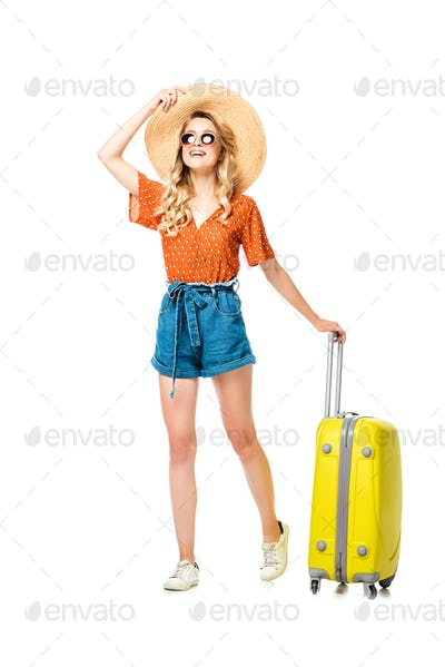 young woman in sunglasses and straw hat with yellow suitcase isolated on white