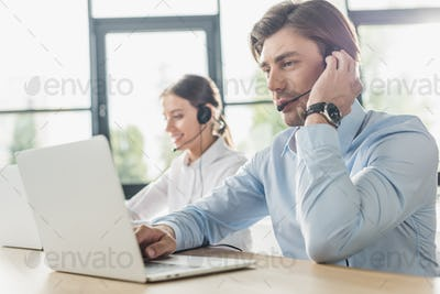 male and female call center managers working together at modern office