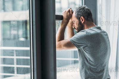 depressed bearded man leaning at window and looking through it