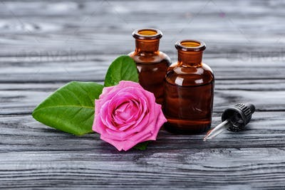 bottles of natural herbal essential oils, pipette and pink rose on wooden surface