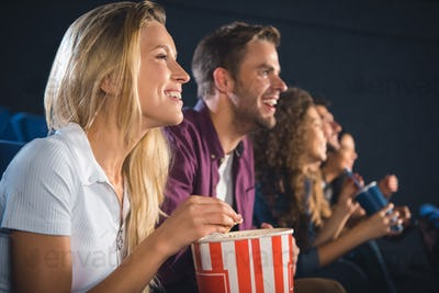cheerful friends with popcorn watching film together in movie theater