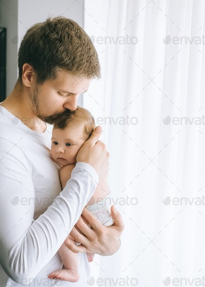 father kissing infant boy in front of curtains at home