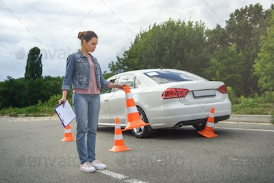 driver holding car insurance and putting traffic cones on road