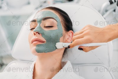 partial view of cosmetologist applying clay mask on female face in spa salon