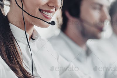 cropped shot of smiling young call center manageress working with colleagues