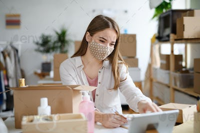 Young woman dropshipper with tablet working at home, coronavirus concept.