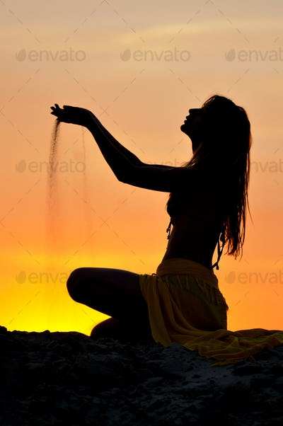 Silhouette of slim woman sitting and playing with sand at sunset