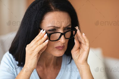 Mature Woman Squinting, Trying To Look Closer Through Eyeglasses