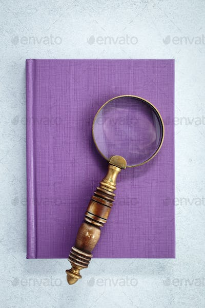 Magnifying glass on purple notebook
