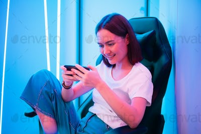 Cybersport gamer playing mobile game on the smart phone sitting on a gaming chair in neon color room