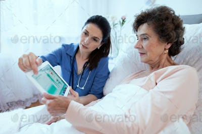 Female Doctor and Senior Patient Discussing Test Results Holding Digital Tablet.