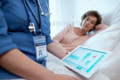 Digital Tablet Showing Test Results of Elderly Female Patient Lying in Bed in the Background.
