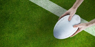 Composite image of a rugby player posing a rugby ball