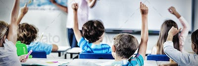 Kids raising hand in classroom
