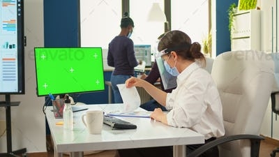 Manager with face mask typing on computer with green screen