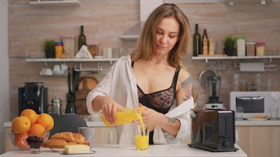 Attractive woman pouring fresh juice