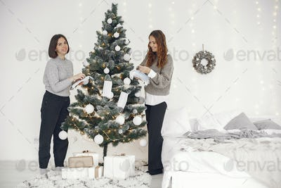 Two women decorate Christmas treee with medical masks