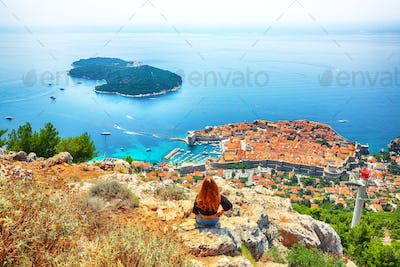 Happy girl enjoys view of old town (medieval Ragusa) and Dalmatian Coast