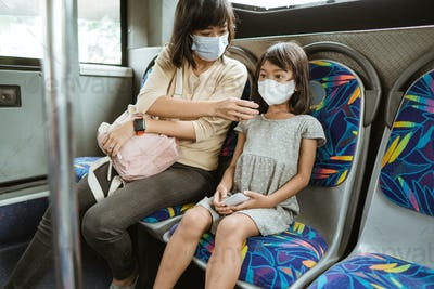 mother and daughter riding public transport during pandemic