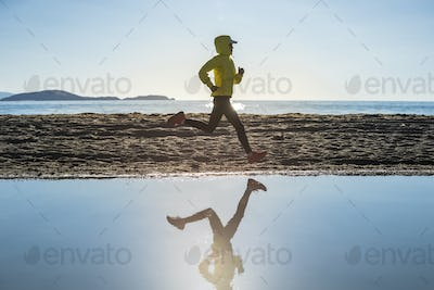Woman trail runner cross country running  in winter lakeside