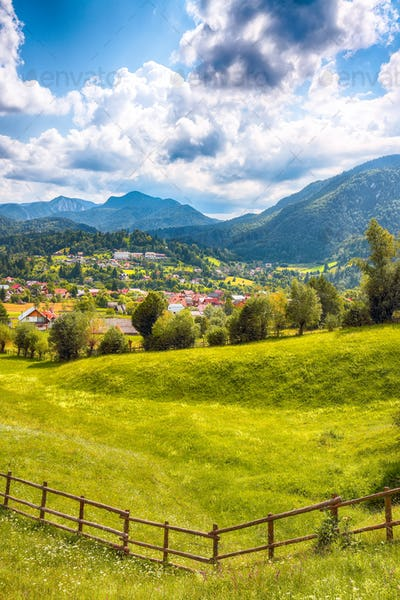 Stunning alpine landscape with green fields and Piatra Craiului mountains in Dambovicioara Commune