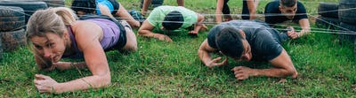 Participants in an obstacle course crawling