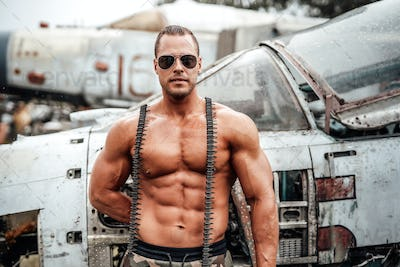 Topless bodybuilder with sunglasses poses near airplane