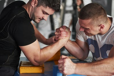 Tense atmosphere. Arm wrestling challenge between two men. Match on a special table