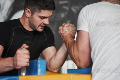 Struggling for win. Arm wrestling challenge between two men. Match on a special table