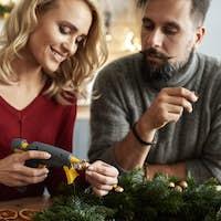 Couple decorating Christmas wreaths using hot glue