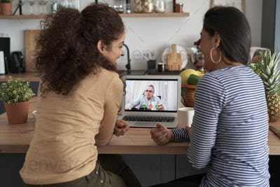Rear view of two women during videoconference with father