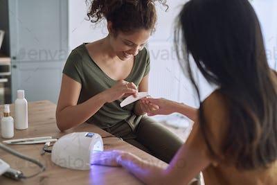 Happy women making nail beauty treatments at home