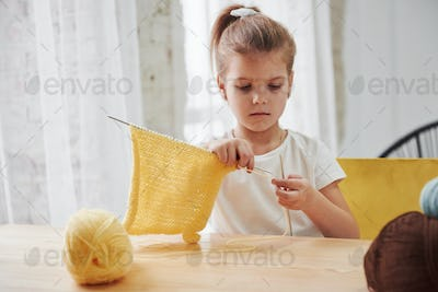 Kid is knitting at home. Cute little girl sitting near the wooden table is learning some new stuff