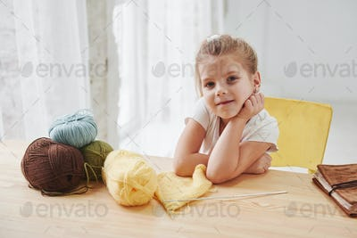 Cute little girl sitting near the wooden table is learning some new stuff