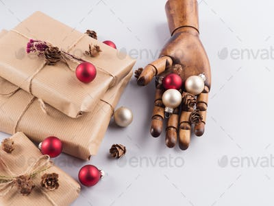 Wrapped xmas gifts and ornament in hand