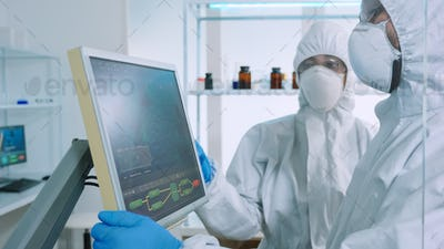 Chemists in ppe suit discussing about changes in vaccine composition