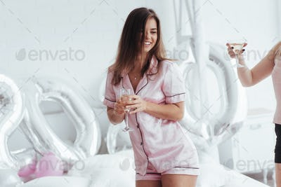 Celebrating bachelorette in white bedroom. Girls smiles and drink champagne